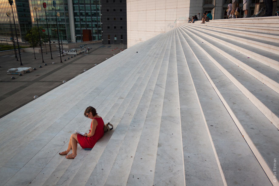 People sit on the steps of the Grande Arche in Paris